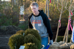 President Karl W. Einolf pushing a wheel barrel of bushes for Habitat for Humanity