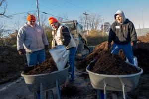 Three staff members prepping two wheelbarrows of soil