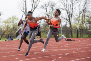 Indiana Tech relay team passing a baton in a race on the outdoor track