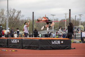 Indiana Tech student athlete clearing the bar after successfully completing a pole vault