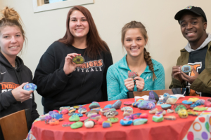 four students holding up their painted hope rocks and smiling