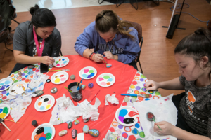 Three students sitting at a table painting their hope rocks