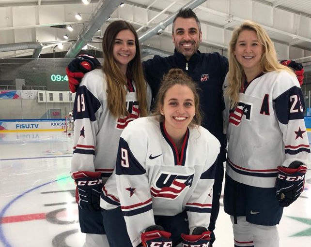 a male, Scott Hicks, the first coach for Indiana Tech's women's hockey, is seen with three female players from the US National team