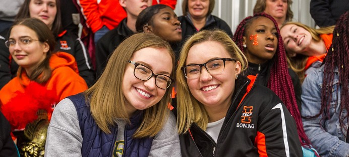 Two students sitting together while attending a sport event at Indiana Tech