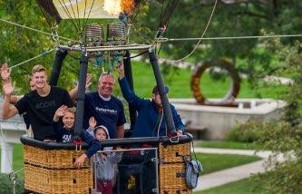Alumni and Family in a hot air balloon at Homecoming